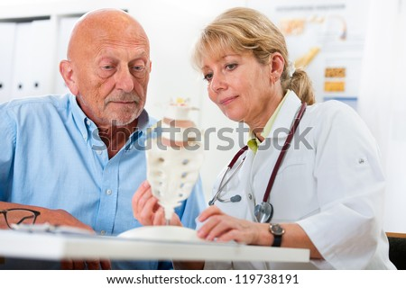 Physical therapist talking to patient and explains the cause of his pain