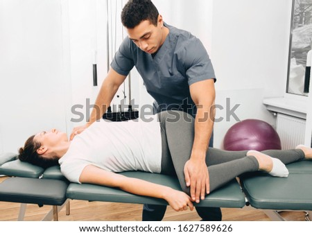 Physical therapist twists the patient's body. Exercises for the treatment of the spine, treatment of osteochondrosis