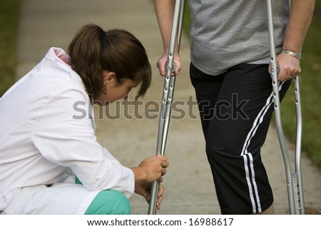 physical therapists adjusts a patient's crutches