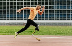 physically disabled athlete running with prosthetic legs