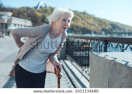 Physically exhausted elderly woman leaning on a cane and looking into vacancy while struggling from a physical discomfort in a low back zone.