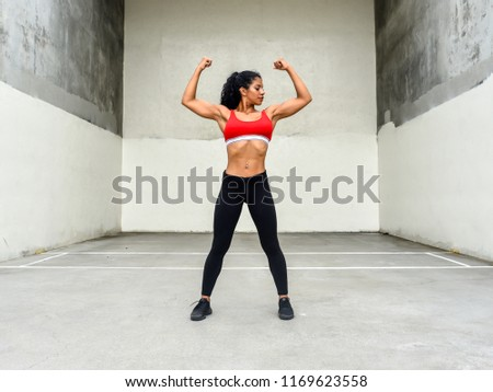 Physically fit woman flexes arm muscles in outdoor gym area