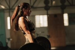 Physically fit woman lifting heavy weights. Fitness female doing heavy weight workout at gym.