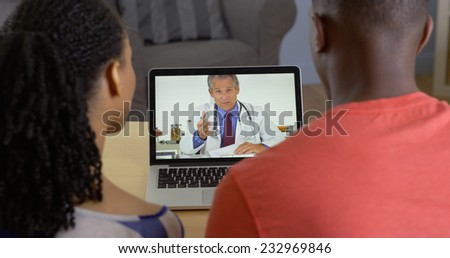 Physician talking with young black couple about medical issues over internet video chat