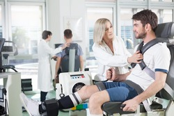 physicians with patients in a gym for physical rehabilitation dynamometer in the foreground and in the background cycle ergometer/ gym physiatric rehabilitation