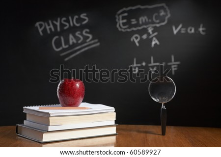 Physics class concept with red apple on pile of books and magnifying glass with equation on blackboard