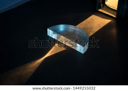 Physics experiment. Passing of a lightbeam through a positive lens, showing a convergent pattern. Light comes together in focal point.