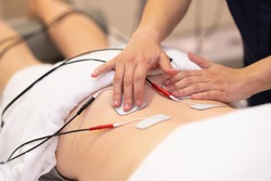 Physiotherapist applying electro stimulation in physical therapy to a young woman.