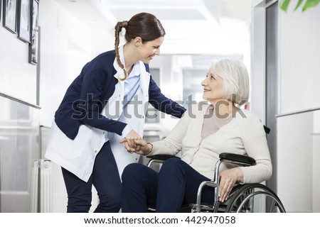 Physiotherapist Consoling Senior Woman Sitting In Wheelchair Stockfoto ©