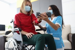Physiotherapist doctor in medical mask helps to raise dumbbell to disabled woman in wheelchair at home portrait. Rehabilitation of disabled people at home during epidemic and coronavirus infection