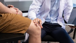 physiotherapist doctor rehabilitation consulting physiotherapy giving exercising knee treatment with patient in physio clinic or hospital