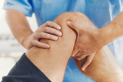 Physiotherapist doing healing treatment on patient leg. Therapist wearing blue uniform. Osteopathy, Chiropractic leg adjustment