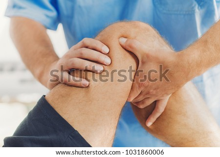 Physiotherapist doing healing treatment on patient leg. Therapist wearing blue uniform. Osteopathy, Chiropractic leg adjustment