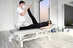physiotherapist doing leg muscle stretching to female patient. Treatment of a woman's sciatic nerve. High quality photo