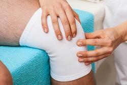 Physiotherapist doing patellar mobilisation after knee injury