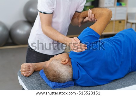 Physiotherapist doing shoulder exercises with an elderly male patient to increase his mobility and restore functionality