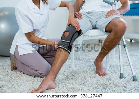 Physiotherapist examining patients knee in clinic