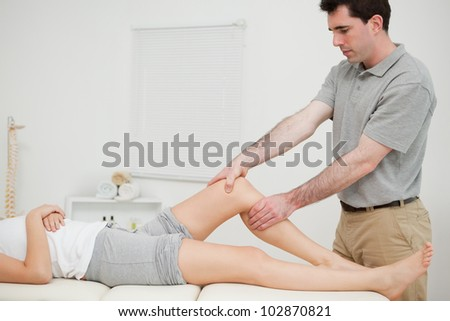 Physiotherapist examining the knee of his patient while touching it in a room