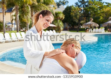 Physiotherapist gives senior woman a massage at the wellness hotel by the pool