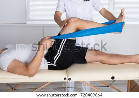 Physiotherapist Helping Patient While Stretching His Leg