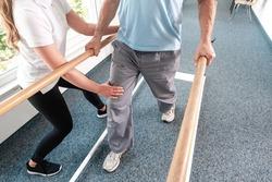 Physiotherapist helping senior man in rehabilitation walking on the bars