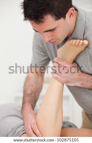 Physiotherapist manipulating the leg of a woman while she is lying in a room