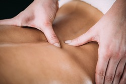 Physiotherapist massaging female patient with injured back muscle. Sports injury treatment.