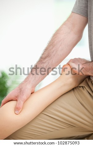 Physiotherapist massaging the leg of a woman in a room
