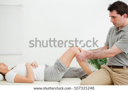 Physiotherapist sitting while massaging a knee in a room