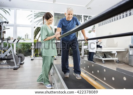 Physiotherapist Standing By Smiling Patient Walking Between Para