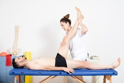Physiotherapist stretching the leg muscles of an athlete lying on the stretcher. Injury prevention treatment before competition.