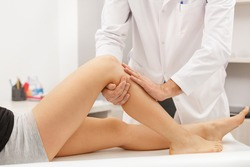 Physiotherapist treating injured knee of female athlete patient. Post traumatic rehabilitation, sport physical therapy. Osteopathy, Chiropractic leg adjustment.