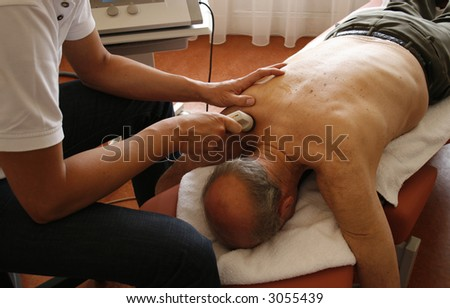 physiotherapist treats shoulder of  senior patient
