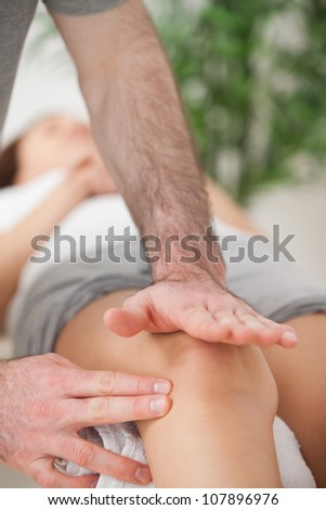 Physiotherapist using his hand palm to massage a knee indoors