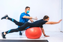 Physiotherapist with mask and a patient stretching on a ball. Physiotherapy with protective measures for the Coronavirus pandemic, COVID-19. Osteopathy, sports chiromassage