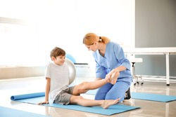 Physiotherapist working with little boy in rehabilitation center