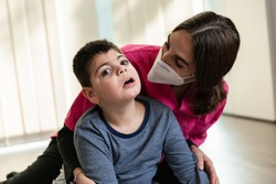 physiotherapist works with disabled child, cerebral palsy. mask fp2 coronavirus