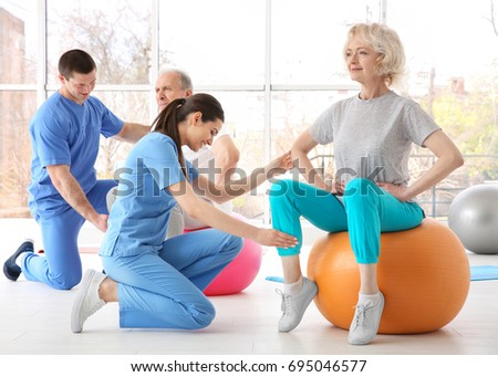 Physiotherapists working with elderly patients in modern clinic Stock photo ©