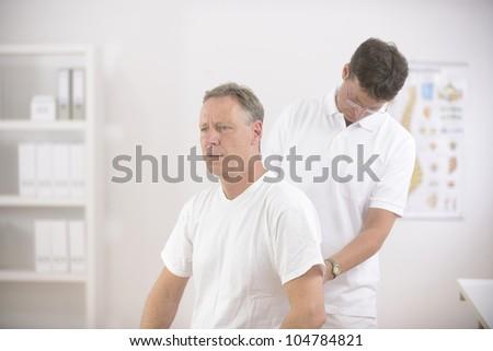 Physiotherapy: Physiotherapist examining senior man at office