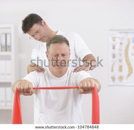 Physiotherapy: Senior man doing exercise under supervision of physiotherapist