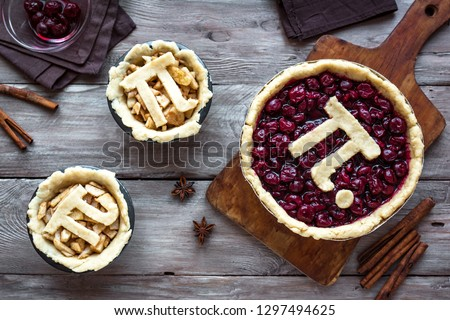 Pi Day Cherry and Apple Pies - making homemade traditional various Pies with Pi sign for March 14th holiday, on wooden background, top view.
