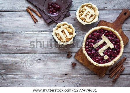Pi Day Cherry and Apple Pies - making homemade traditional various Pies with Pi sign for March 14th holiday, on rustic wooden background, top view, copy space.