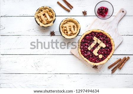 Pi Day Cherry and Apple Pies - making homemade traditional various Pies with Pi sign for March 14th holiday, on white wooden background, top view, copy space.