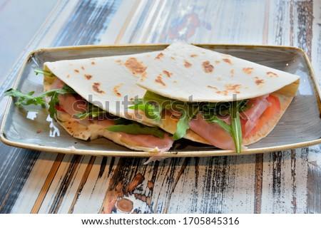 Piadina or Piada, thin Italian flatbread with smocked ham, arugula and ricotta cheese in San Marino Foto stock ©