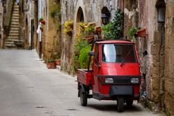 Piaggio Ape standing at the empty street of old italian town