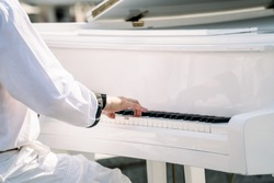 Pianist hands in white clothes play on white piano