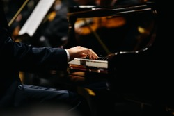 Pianist playing a piece on a grand piano at a concert, seen from the side.