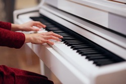 Pianist playing on a white piano. Hands close up.