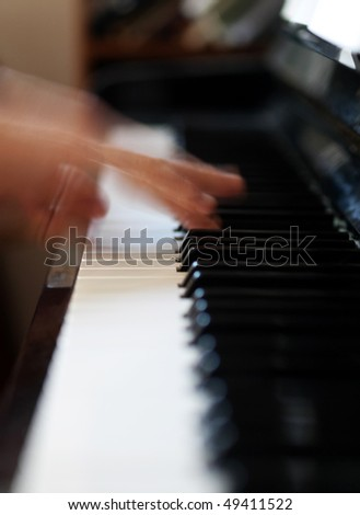 Pianist playing with blurry motion and selective focus on fingers on notes