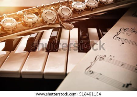Piano and flute with golden shine and sheet music. Horizontal Composition.Front view
